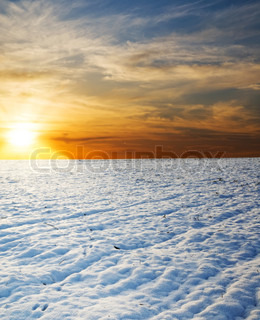 sunset over field under snow