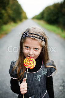 An image of little girl with candy in his hand