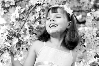 The beautiful little girl, with bush blossoming apple-tree, smiles, black-and-white photo