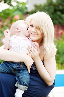 Happy young woman sitting with baby boy in spring flowery garden