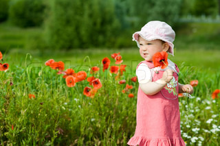 An image of baby-girl amongst green field with red poppies