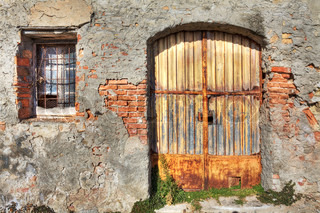 Old brick wall with metal rusty gate and small window in town of La Morra, Northern Italy