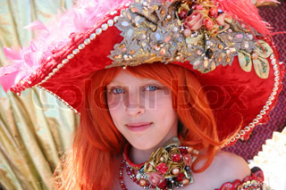 Smiling red-haired teenage girl wearing an antique princess dress and hat