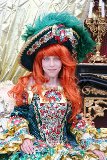 Smiling red-haired teenage girl wearing an antique princess dress and hat (sitting on a princess throne)