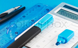 Office supplies with calculator on blue background