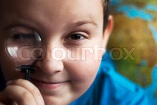 Nine-year-old boy looking through a magnifying glass with secret expression