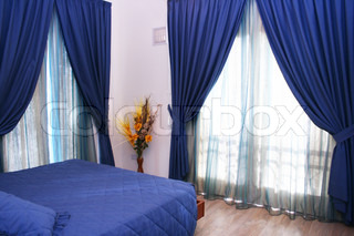 Bedroom with blue curtains and bedspread