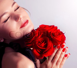 Beautiful female holding red roses bouquet, valentine romantic rose gift, woman over pink abstract background with closed eyes, happy young girl with flowers dreaming