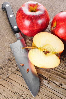 Ripe apple fruits and knife at old wooden table with canvas