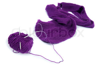 Close-up photos of the coil of purple yarn with knitting needles on the white background