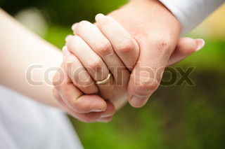 Bride and groom are holding hands each other