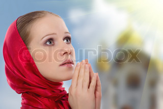beautiful young woman in a scarf prays to God on the background of the domes of the church