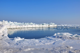 Pierce frozen in ice at sea and blue sky