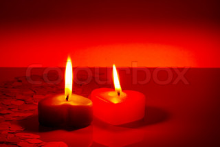 Two burning heart shaped candles over red background