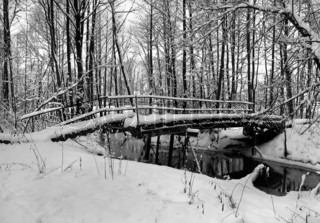 Winter landscape with small river and footpath bridge