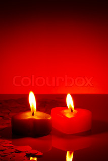 Two burning heart shaped candle on a red table