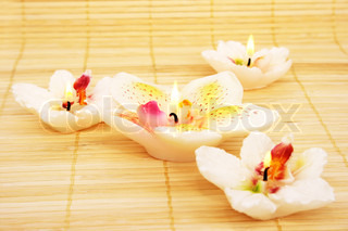 Orchid candles on bamboo background