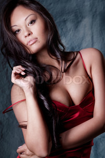 young gorgeous brunette in red evening dress posing