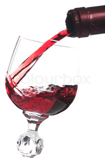 Red wine pouring down from a bottle into a glass over white background