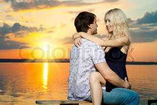 romantic evening date on nature, couple on beautiful sunset or sunrise on shore