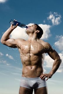 the very muscular handsome sexy guy on sky background, drink water, focus on face
