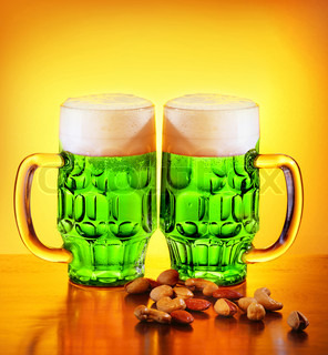 Irish green beer, traditional alcohol for stPatrick's day holiday celebration, lucky clover beverage, two glasses with nuts, food and drink still life