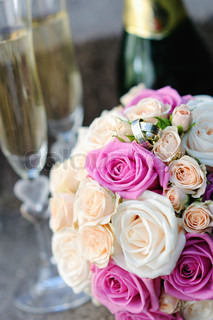 bridal bouquet of white and pink roses with wedding rings