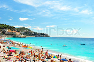 View of the beach in Nice, France, near the Promenade des Anglais tourists, sunbeds and umbrellas on summer hot day