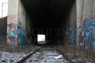 Graffiti and railroad track in dark tunnel with snow on the ground