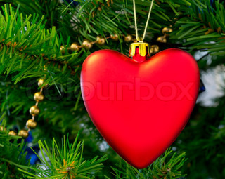 The Christmas-tree decoration in the form of red heart hangs on a green fur-tree branch