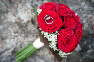 Bridal bouquet made with red roses with wedding rings