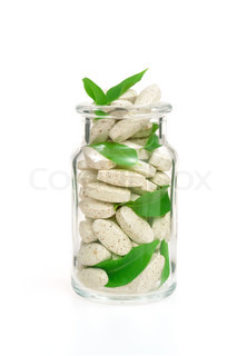 Herbal supplement pills and fresh leaves  in glass – alternative medicine concept