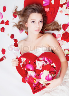 Beautiful girl with rose petals in heart form box