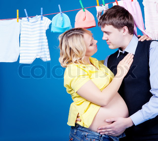 Pregnant woman with husband with child clothes