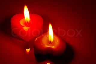 Two burning heart shaped candles on a red table