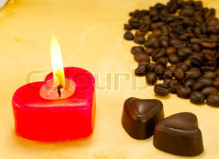 Burning candle, two heart shaped candies and cofee beans on grungy paper