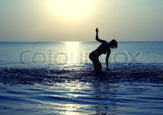 Silhouette of the happy woman playing with water at summer beach