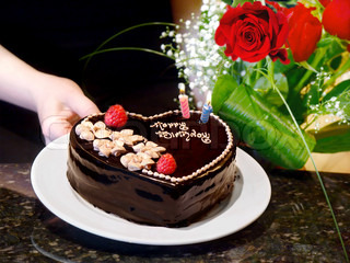Birthday cake and roses. Female hands holding  chocolate heart cake and roses