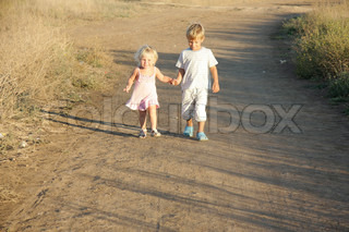 young brother and sister walking by country road