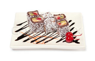 Chocolate roll with fruit filling sprinkle coconut on a plate with sauce and a cherry The traditions of cuisine in Japan