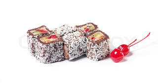 Chocolate roll with fruit filling sprinkle coconut with two cherries on a white background The traditions of cuisine in Japan