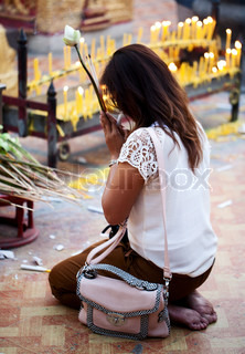 CHIANG MAI, THAILAND - FEBRUARY 4: Buddhist woman praying on evening religion ceremony in Doi Suthep Wat on February 4, 2012 in Chiang Mai, Thailand