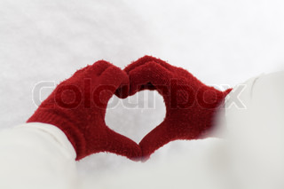 Hands in red gloves forming a shape of heart