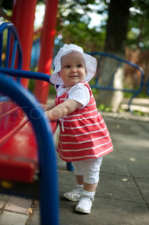 Little baby girl is standing near bench at playground
