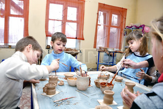 group of children shaping clay pots and vases in pottery studio school