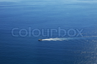 Aerial view on touristic cruise ship sailing on beautiful blue surface of Mediterranean sea in Northern Italy