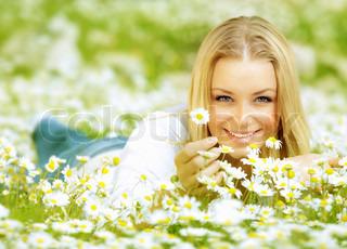 Smuk kvinde nyder daisy felt , nice kvindelige ligger ned i engen med blomster, smukke pige afslappende udendørs , have det sjovt, hånd holder plante , lykkelig ung dame og foråret grøn natur , harmoni koncept