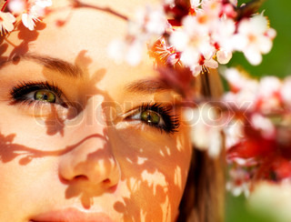 Pretty female face with cherry blossom tree, closeup outdoor portrait