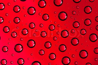 Abstract macro of water drops over red background