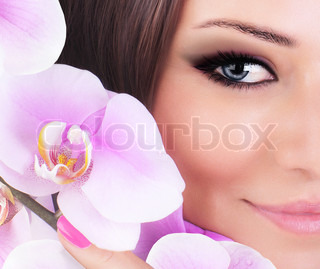 Half face of gorgeous young model, beautiful woman eye with fresh pink orchid flower,part of female head, sexy girl with stylish look, spa and beauty background